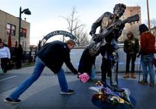 David Gaule, from Springfield, Ill. drops off flowers at the statue of music legend Chuck Berry on the Delmar Loop, in University City on Saturday, March 18, 2017. Berry died earlier today at the age of 90. After hearing Berry died Gaule drove to St. Louis from Springfield to pay his respects. (David Carson/St. Louis Post-Dispatch via AP)
