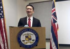 FILE - In this Feb. 3, 2017, file photo, Hawaii Attorney General Doug Chin speaks at a news conference in Honolulu announcing the state of Hawaii has filed a lawsuit challenging President Donald Trump's travel ban. The state of Hawaii has become the first state to sue to stop Trump's revised travel ban. Attorneys for the state filed the lawsuit Wednesday, March 8, 2017, in federal court in Honolulu. The state had previously sued over Trump's initial travel ban, but that lawsuit was put on hold while other cases played out across the country. (AP Photo/Audrey McAvoy, File)