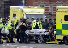 """Emergency services transport an injured person to an ambulance, close to the Houses of Parliament in London, Wednesday, March 22, 2017. London police say they are treating a gun and knife incident at Britain's Parliament """"as a terrorist incident until we know otherwise."""" The Metropolitan Police says in a statement that the incident is ongoing. Officials say a man with a knife attacked a police officer at Parliament and was shot by officers. Nearby, witnesses say a vehicle struck several people on the Westminster Bridge. (AP Photo/Matt Dunham)"""