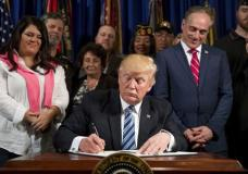 """President Donald Trump, accompanied by Veterans Affairs Secretary David Shulkin, center right, and veterans, signs an Executive Order on """"Improving Accountability and Whistleblower Protection"""" at the Department of Veterans Affairs, Thursday, April 27, 2017, in Washington. (AP Photo/Andrew Harnik)"""
