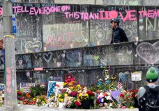 A bicyclist walking his bike down a ramp in Portland, Ore., Wednesday, May 30, 2017, is surrounded by messages, flowers, images and candles at the memorial for two men fatally stabbed on a light rail train in Portland last week. The man, charged with fatally stabbing the two men and injuring a third who tried to shield young women from an anti-Muslim tirade, appeared to brag about the attacks as he sat in the back of a police patrol car according to court documents.(AP Photo/Don Ryan)