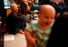 FILE - In this May 22, 2016 file photo, Denise Wilkes, left, looks at baby Noah Burton, sitting on a fellow worshiper's lap, during a church service in Birmingham, Ala. Emma and Noah continued their reign as the most popular baby names last year. (AP Photo/Brynn Anderson, File)