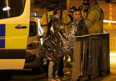 Two women wrapped in thermal blankets stand near the Manchester Arena, where U.S. singer Ariana Grande had been performing, in Manchester, northern England, Britain, May 23, 2017. REUTERS/Andrew Yates