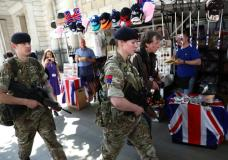 Soldiers walk past tourist souvenir stalls in London, Britain May 24, 2017. REUTERS/Neil Hall
