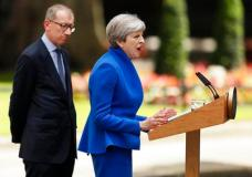 British Prime Minister Theresa May speaks watched by her husband Philip in 10 Downing street, London, as she addresses the press Friday, June 9, 2017 following an audience with Britain's Queen Elizabeth II at Buckingham Palace where she asked to form a government. May's gamble in calling an early election backfired spectacularly, as her Conservative Party lost its majority in Parliament. (AP Photo/Tim Ireland)
