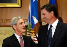 FILE - In this Sept. 4, 2013, file photo, then-incoming FBI Director James Comey talks with outgoing FBI Director Robert Mueller before Comey was officially sworn in at the Justice Department in Washington. Mueller, the somber-faced and demanding FBI director who led the bureau through the Sept. 11 attacks, and Comey, his more approachable and outwardly affable successor, may be poles apart stylistically but both command a wealth of respect in the law enforcement and legal community. (AP Photo/Susan Walsh, File)