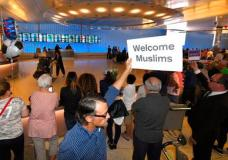 John Wider holds up a sign becoming Muslims in the Tom Bradley International Terminal at Los Angeles International Airport, Thursday, June 29, 2017, in Los Angeles. A scaled-back version of President Donald Trump's travel ban took effect Thursday evening, stripped of provisions that brought protests and chaos at airports worldwide in January yet still likely to generate a new round of court fights. (AP Photo/Mark J. Terrill)