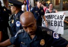 Capitol Hill police officers prepare to arrest a group protesting the republican healthcare bill outside the offices of Sen. Dean Heller, R-Nev., on Capitol Hill in Washington, Monday, July 17, 2017. The Senate has been forced to put the Republican's health care bill on hold for as much as two weeks until Sen. John McCain, R-Ariz., can return from surgery. (AP Photo/Andrew Harnik)