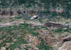 A helicopter flies above the rugged terrain along the banks of the East Verde River during a search and rescue operation for victims of a flash flood on Sunday, July 16, 2017, in Payson, Ariz. Search and rescue crews, including 40 people on foot and others in a helicopter, have recovered bodies of children and adults, some as far as two miles down the river after Saturday's flash flooding poured over a popular swimming area inside the Tonto National Forest in central Arizona. (AP Photo/Ralph Freso)