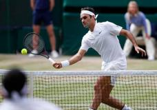 Switzerland's Roger Federer returns to Canada's Milos Raonic during their Men's Singles Quarterfinal Match on day nine at the Wimbledon Tennis Championships in London Wednesday, July 12, 2017. (AP Photo/Kirsty Wigglesworth)