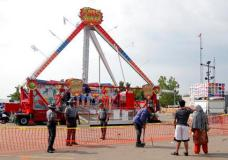 Passers by look at the fire ball ride as Ohio State Highway Patrol troopers stand guard at the Ohio State Fair Thursday, July 27, 2017, in Columbus, Ohio.   The fair opened Thursday but its amusement rides remained closed one day after Tyler Jarrell, 18, was killed and seven other people were injured when the thrill ride broke apart and flung people into the air. (AP Photo/Jay LaPrete)