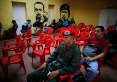 Voters wait to cast their ballots next murals of Venezuelan Independence hero Ezequiel Zamora, left, and the late Venezuelan President Hugo Chavez at a polling station in Caracas, Venezuela, Sunday, July 30, 2017. President Nicolas Maduro asked for global acceptance on Sunday as he cast an unusual pre-dawn vote for an all-powerful constitutional assembly that his opponents fear he'll use to replace Venezuelan democracy with a single-party authoritarian system. (AP Photo/Ariana Cubillos)