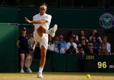 Switzerland's Roger Federer kicks the ball after an inconsistent bounce as he plays his Men's Singles semifinal match against Czech Republic's Tomas Berdych on day eleven at the Wimbledon Tennis Championships in London, Friday, July 14, 2017. (AP Photo/Alastair Grant)