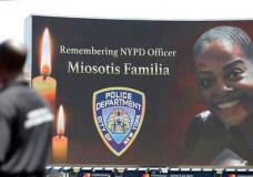 """A security guard stands at attention as New York Police Department officer Miosotis Familia is memorialized before the start of a baseball game between the New York Yankees and the Toronto Blue Jays in New York, Wednesday, July 5, 2017. Familia was killed in an """"unprovoked attack,"""" in the Bronx borough of New York, according to the NYPD Commissioner. (AP Photo/Kathy Willens)"""