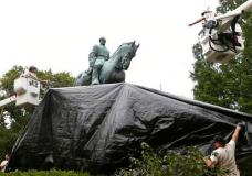 City workers drape a tarp over the statue of Confederate General Robert E. Lee in Emancipation park in Charlottesville, Va., Wednesday, Aug. 23, 2017. The move intended to symbolize the city's mourning for Heather Heyer, killed while protesting a white nationalist rally earlier this month.  (AP Photo/Steve Helber)