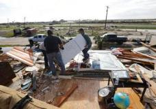 Lupe Tijerina, left, and Andy Guerra, center, and Felix Tijerina, right, work to salvage items from their family home that was destroyed in the wake of Hurricane Harvey, Tuesday, Aug. 29, 2017, in Rockport, Texas. (AP Photo/Eric Gay)