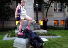 Claire Meddock, 21, stands on a toppled Confederate statue on Monday, Aug. 14, 2017, in Durham, N.C. Activists on Monday evening used a rope to pull down the monument outside a Durham courthouse. The Durham protest was in response to a white nationalist rally held in Charlottesville, Va, over the weekend. Authorities say one woman was killed Saturday after one of the white nationalists drove his car into a group of counterprotesters. (AP Photo/Jonathan Drew)