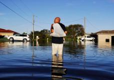 """Jean Chatelier walks through a flooded street from Hurricane Irma after retrieving his uniform from his house to return to work today at a supermarket in Fort Myers, Fla., Tuesday, Sept. 12, 2017. Chatelier walked about a mile each way in knee-high water as a Publix supermarket was planning on reopening to the public today. """"I want to go back to work. I want to help,"""" said Chatelier. (AP Photo/David Goldman)"""