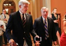 FILE - In this July 13, 2017, file photo, Sen. Bill Cassidy, R-La., left, and Sen. Lindsey Graham, R-S.C., right, talk while walking to a meeting on Capitol Hill in Washington. Senate Republicans are planning a final, uphill push to erase President Barack Obama's health care law. But Democrats and their allies are going all-out to stop the drive. The initial Republican effort crashed in July in the GOP-run Senate. Majority Leader Mitch McConnell said after that defeat that he'd not revisit the issue without the votes to succeed. Graham and Cassidy are leading the new GOP charge and they'd transform much of Obama's law into block grants and let states decide how to spend the money. (AP Photo/Pablo Martinez Monsivais, File)