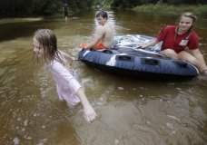 Crimson Peters, 7, left, Tracy Neilsen, 13, center, and Macee Nelson, 15, ride in an inner tube down a flooded street after Hurricane Nate, Sunday, Oct. 8, 2017, in Coden, Ala. (AP Photo/Brynn Anderson)