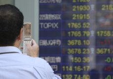 A man takes a picture of an electronic stock board of a securities firm in Tokyo, Friday, Oct. 27, 2017. Shares in Asia posted strong gains early Friday, tracking the upbeat session overnight on Wall Street. Japan's Nikkei 225 index jumped 0.9 percent to 21,945.20 as the U.S. dollar strengthened against the yen, boosting exporters' shares. Investors are watching for U.S. GDP data. (AP Photo/Koji Sasahara)