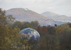 A globe and a Ferris Wheel stand in the forest near Bonn, Germany, Monday, Nov. 13, 2017. The UN Climate Conference takes place in Bonn, Germany till Nov. 17, 2017. (Rainer Jensen/dpa via AP)