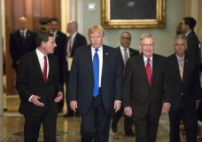 President Donald Trump, center, escorted by Sen. John Barrasso, R-Wyo., chairman of the Senate Republican Policy Committee, left, and Senate Majority Leader Mitch McConnell, R-Ky., right, arrives at the Capitol to meet with GOP lawmakers about moving his agenda and passing the Republican tax bill, in Washington, Tuesday, Nov. 28, 2017. (AP Photo/J. Scott Applewhite)