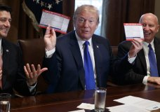 President Donald Trump holds an example of what a new tax form may look like during a meeting on tax policy with Republican lawmakers including House Speaker Paul Ryan of Wis., and Chairman of the House Ways and Means Committee Rep. Kevin Brady, R-Texas, right, in the Cabinet Room of the White House, Thursday, Nov. 2, 2017, in Washington. (AP Photo/Evan Vucci)