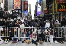Spectators gather ahead of the New Year's Eve celebration in Times Square in New York, on Sunday, Dec. 31, 2017. New Yorkers, celebrity entertainers and tourists from around the world will pack into Times Square for what's expected to be a flashy but frigid celebration marking the start to the new year. (AP Photo/Peter Morgan)