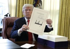 """President Donald Trump displays the $1.5 trillion tax overhaul package he had just signed, Friday, Dec. 22, 2017, in the Oval Office of the White House in Washington. Trump touted the size of the tax cut, declaring to reporters in the Oval Office before he signed it Friday that """"the numbers will speak."""" (AP Photo/Evan Vucci)"""