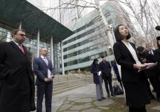 FILE- In this Dec. 21, 2017, file photo, Mariko Hirose, right, a litigation director at the Urban Justice Center, addresses reporters as Mark Hetfield, president & CEO of HIAS, left, and Rabbi Will Berkowitz, Jewish Family Service of Seattle CEO, look on in front of a federal courthouse after speaking with media in Seattle. The government has asked a federal judge to change his order that partially lifted a Trump administration refugee ban. (AP Photo/Elaine Thompson, File)