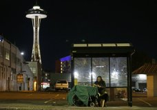 FILE - In this Oct. 30, 2017 file photo, Dave Chung, who says he has been homeless for five years on the streets of California and Washington state, eats a meal before bedding down in a bus shelter in view of the Space Needle in Seattle. On Thursday, Jan. 11, 2018, President Donald Trump's administration announced $2 billion in grants for local programs to deal with homelessness. The funding total is a record for the Continuum of Care grants, but only a small increase over recent years. The announcement comes as the administration is calling for cuts to housing programs and as the West Coast is dealing with a homeless crisis. (AP Photo/Ted S. Warren, File)