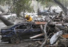 A member of the Long Beach Search and Rescue team looks for survivors in a car in Montecito, Calif. on Tuesday, Jan. 9, 2018. Several homes were swept away before dawn Tuesday when mud and debris roared into neighborhoods in Montecito from hillsides stripped of vegetation during a recent wildfire. (Daniel Dreifuss)