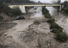 In this photo provided by Santa Barbara County Fire Department, U.S. 101 freeway at the Olive Mill Road overpass is flooded with runoff water from Montecito Creek in Montecito, Calif. on Tuesday, Jan. 9, 2018. Several homes were swept away before dawn Tuesday when mud and debris roared into neighborhoods in Montecito from hillsides stripped of vegetation during a recent wildfire. (Mike Eliason/Santa Barbara County Fire Department via AP)