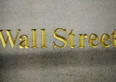 FILE - In this Oct. 8, 2014, file photo, a Wall Street address is carved in the side of a building in New York. Stock indexes are wavering between small gains and losses in early trading on Wall Street, Thursday, Jan. 18, 2018, as gains for technology companies are offset by losses in energy and other sectors. (AP Photo/Mark Lennihan, File)