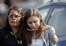 Mourners hug as they leave the funeral of Alaina Petty, in Coral Springs, Fla., Monday, Feb. 19, 2018. Petty was a victim of Wednesday's mass shooting at Marjory Stoneman Douglas High School. Nikolas Cruz, a former student, was charged with 17 counts of premeditated murder on Thursday. (AP Photo/Gerald Herbert)