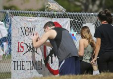 A man signs a banner as people pay tribute at a memorial for the victims of the shooting at Marjory Stoneman Douglas High School on Sunday, Feb. 25, 2018, in Parkland, Fla. (David Santiago/Miami Herald via AP)