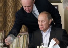 """FILE - In this Friday, Nov. 11, 2011, file photo, Yevgeny Prigozhin, left, serves food to Russian Prime Minister Vladimir Putin during dinner at Prigozhin's restaurant outside Moscow, Russia. Progozhin is known as """"Putin's chef"""" _ a wealthy Russian businessman and restaurateur who gained favor with Putin through his stomach. On Feb. 16, 2016, Prigozhin, along with 12 other Russians and three Russian organizations, was charged by the U.S. government as part of a vast and wide-ranging effort to sway political opinion during the 2016 U.S. presidential election. According to the indictment, Prigozhin and his companies provided significant funding to the Internet Research Agency, a St. Petersburg-based troll farm that allegedly used bogus social media postings and advertisements fraudulently purchased in the name of Americans to influence the White House race. (AP Photo/Misha Japaridze, Pool, File)"""