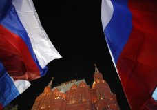 People wave Russian flags in front of the State Historical Museum near the Kremlin in Moscow, Sunday, March 18, 2018. An exit poll suggests that Vladimir Putin has handily won a fourth term as Russia's president, adding six more years in the Kremlin for the man who has led the world's largest country for all of the 21st century. (AP Photo/Pavel Golovkin)