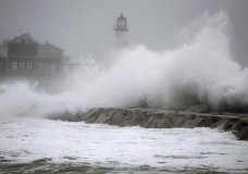 Waves crash against a seawall near the Scituate Lighthouse, Friday, March 2, 2018, in Scituate, Mass. A major nor'easter pounded the East Coast on Friday, packing heavy rain and strong winds as residents from the mid-Atlantic to Maine braced for coastal flooding. (AP Photo/Steven Senne)