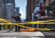 Police officers stand by a covered body in Toronto after a van mounted a sidewalk and crashed into a crowd of pedestrians on Monday, April 23, 2018. The van apparently jumped a curb Monday in a busy intersection in Toronto, struck the pedestrians and fled the scene before it was found and the driver was taken into custody, Canadian police said. (Aaron Vincent Elkaim/The Canadian Press via AP)