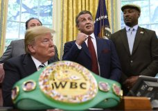 President Donald Trump, left, and heavyweight champion boxer, Lennox Lewis, right, watch as Sylvester Stallone gestures in the Oval Office of the White House in Washington, Thursday, May 24, 2018, where Trump granted a posthumous pardon to Jack Johnson, boxing's first black heavyweight champion. (AP Photo/Susan Walsh)