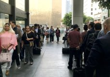 In this Tuesday, June 19, 2018 photo, immigrants awaiting deportation hearings, line up outside the building that houses the immigration courts in Los Angeles. Inside the courtroom, immigrant children who arrived on the U.S. border seeking asylum or other relief attended a special hearing for juveniles on the status of their cases. (AP Photo/Amy Taxin)