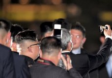 North Korean leader Kim Jong Un, seen from back, takes a selfie with Singapore Foreign Minister Vivian Balakrishnan as they walk on the Jubilee Bridge as he tours Singapore on Monday, June 11, 2018, ahead of the summit between U.S. leader Trump and North Korea leader Kim Jong Un. (AP Photo/Joseph Nair)