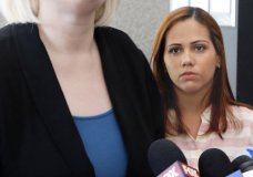 Lidia Karine Souza watches as one of her attorneys speaks outside U.S. District Court in Chicago, Thursday, June 28, 2018. Souza, who is from Brazil, and her son, Diogo, entered the United States in New Mexico in late May and were separated a few days later. The boy has been in a Chicago shelter for about a month. Souza, an asylum-seeker due to dangers that she says they face in Brazil, is fighting to get her son back. A judge heard arguments Thursday and said he would issue a ruling soon. (AP Photo/Martha Irvine)