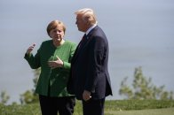 President Donald Trump, right, talks with German Chancellor Angela Merkel after the family photo during the G-7 summit, Friday, June 8, 2018, in Charlevoix, Canada. (AP Photo/Evan Vucci)