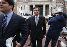 "FILE - In this March 8, 2018, file photo, Jason Maloni, left, former Trump campaign chairman Paul Manafort's spokesman, left, walks with Paul Manafort, center, as they leave the Alexandria Federal Courthouse after an arraignment hearing in Alexandria, Va. A federal judge in Virginia has rejected Manfort's move to throw out charges brought by the special counsel in the Russia investigation. The decision June 26 was a setback for Manafort in his defense against numerous tax and bank fraud charges. Behind Manafort protester Bill Christeson holds up a sign that says ""traitor."" (AP Photo/Jacquelyn Martin)"