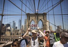 Activists carry signs across the Brooklyn Bridge during a rally to protest the Trump administration's immigration policies Saturday, June 30, 2018, in New York, New York. (AP Photo/Kevin Hagen)