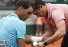 Spain's Rafael Nadal gets medical attention for an injury on the lower part of his left arm during his quarterfinal match of the French Open tennis tournament against Argentina's Diego Schwartzman at the Roland Garros stadium in Paris, France, Wednesday, June 6, 2018. (AP Photo/Thibault Camus)