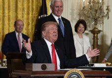 """President Donald Trump gestures as he signs a """"Space Policy Directive"""" during a meeting of the National Space Council in the East Room of the White House, Monday, June 18, 2018, in Washington, as Vice President Mike Pence watches. AP Photo/Susan Walsh)"""